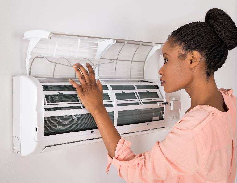 Woman opening up an HVAC unit representing adhesives for the HVAC industry from H.B. Fuller.