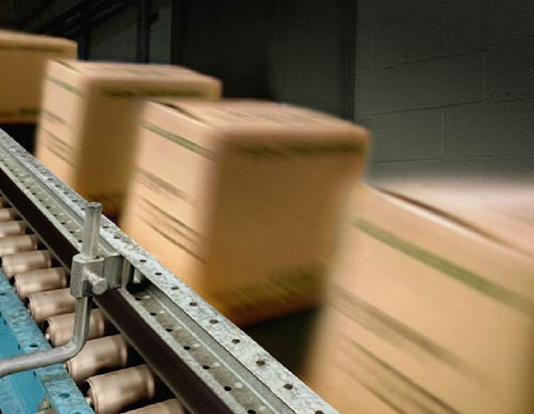 Cases on a conveyor belt representing case and carton sealing packaging adhesives from H.B. Fuller.