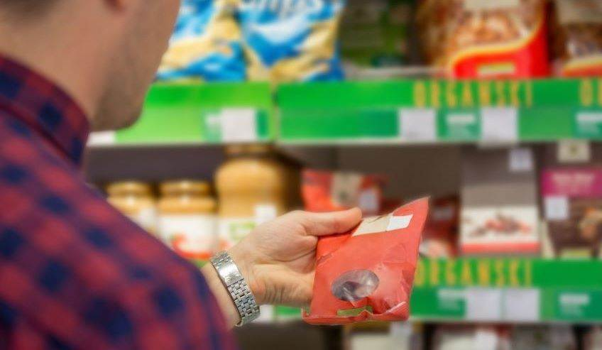 Consumer holding flexible packaging in left hand.